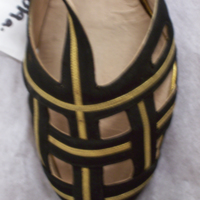 Detail View of Black and Gold T-Strap Sandals